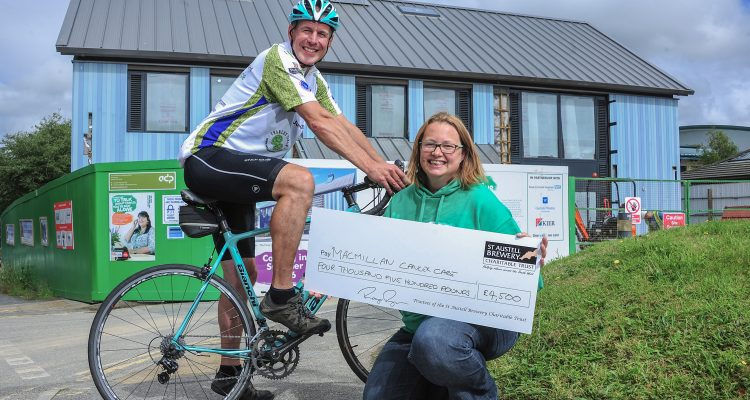 Roger Ryman hands over the cheque to Emma Wright outside the nearly completed centre in Cornwall